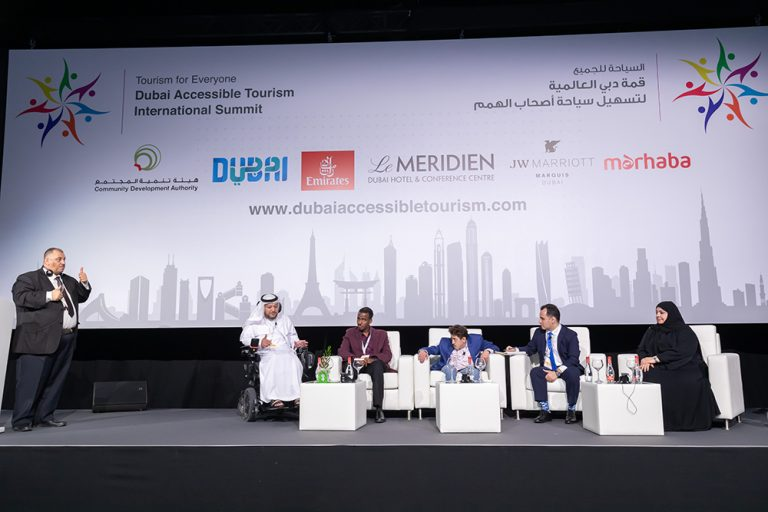 a group of speakers discussing the accessible tourism